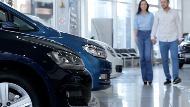 Couple walks along the row of cars at the dealership Young couple walking along the row of cars at the dealership. Bearded caucasian man holding his girlfriends hand in his hand. Man and woman walking on background of white, blue and black cars car dealership stock videos & royalty-free footage