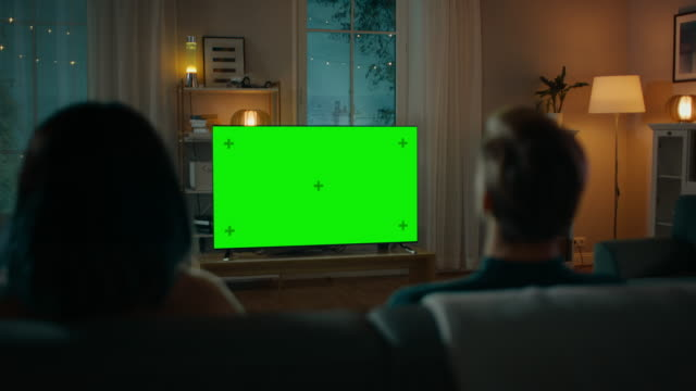 couple watches green mock-up screen tv while sitting on a couch in the living room. romantic evening for boyfriend and girlfriend. - oglądać filmów i materiałów b-roll