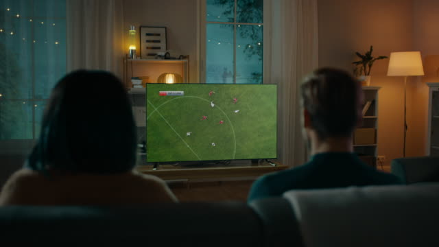 Couple Watches Professional Soccer Match on TV while Sitting on a Couch at Home in the Evening. Boyfriend and Girlfriend Football Fans Watch Sports Even. Back View Shot. Couple Watches Professional Soccer Match on TV while Sitting on a Couch at Home in the Evening. Boyfriend and Girlfriend Football Fans Watch Sports Even. Back View Shot. Shot on RED EPIC-W 8K Helium Cinema Camera. family watching tv stock videos & royalty-free footage