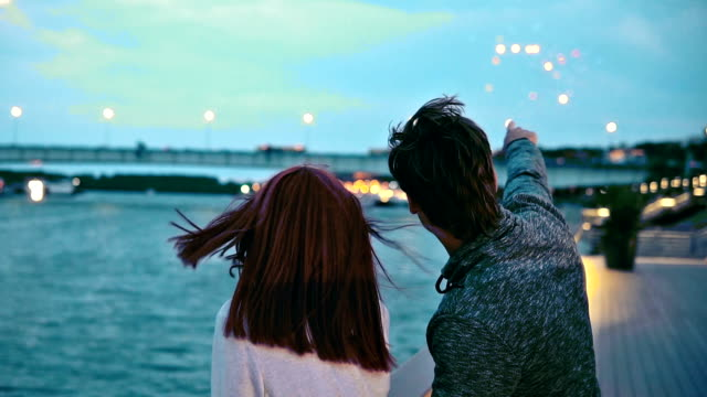 Couple watching fireworks at sunset The happy young couple is watching beautiful fireworks beside the ocean and hugging each other. dyed red hair stock videos & royalty-free footage