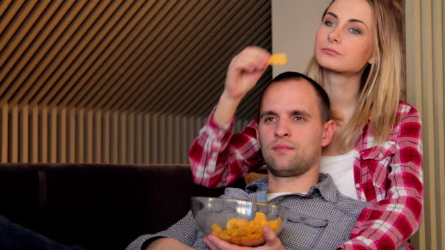 Couple watching movie on couch while eating snacks video