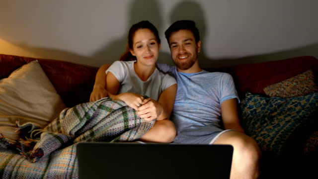 Couple watching movie on laptop at home 4k Happy couple watching movie on laptop at home 4k blanket stock videos & royalty-free footage