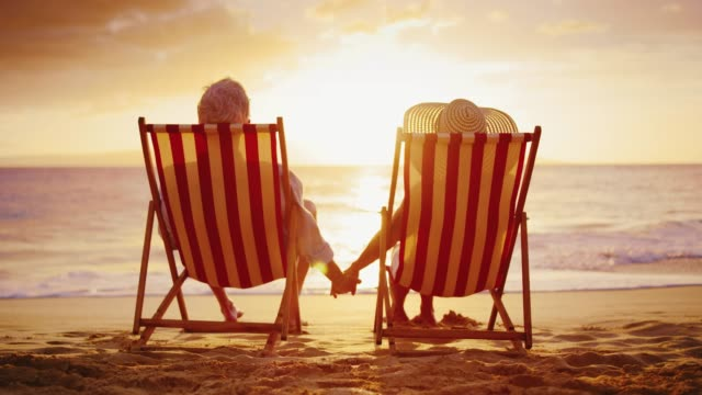 Couple Watching the Sunset on Vacation Romantic couple enjoying beautiful tropical sunset on vacation retirement stock videos & royalty-free footage