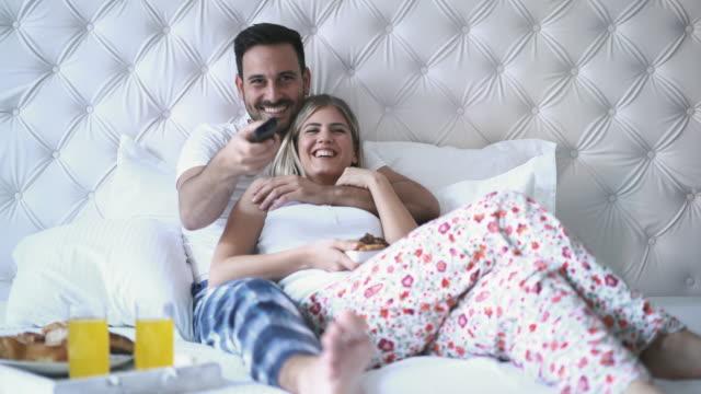 couple watching tv in bedroom. - время дня стоковые видео и кадры b-roll