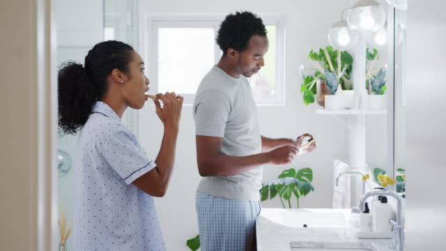 couple wearing pyjamas standing in bathroom at sink brushing teeth in the morning - lavandino video stock e b–roll