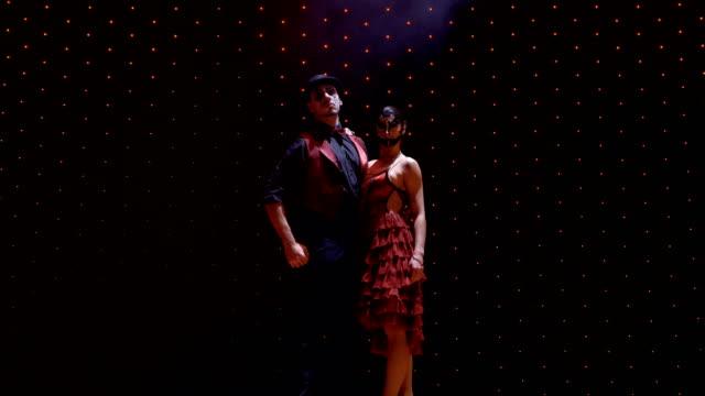 stockvideo's en b-roll-footage met paar dragen schilderachtige kostuums poseren voor de camera op het podium in het licht van schijnwerpers - vetschmink