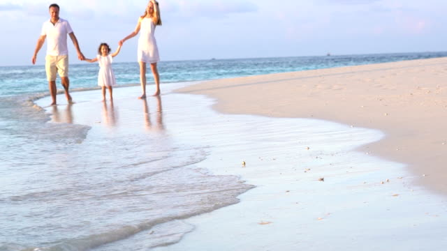 A couple with a small child walking along the beach. Slow motion. video