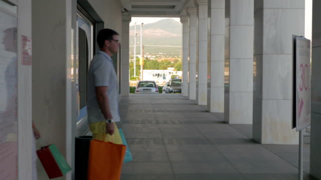 Couple with bags leaving shopping centre Young man and woman walking out the shopping mall. It was enjoyable shopping as they carrying many bags goodbye single word stock videos & royalty-free footage