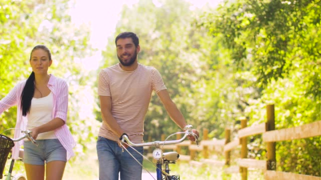 couple with bicycles walking along summer park people, leisure and lifestyle concept - happy young couple with bicycles walking along summer park natural parkland stock videos & royalty-free footage
