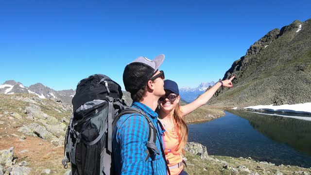 A couple with big backpacks hiking in the Austrian Alps near Schladming. They are enjoying the view on Alpine lake and high mountains around them. They are happy. Camping in the wilderness.