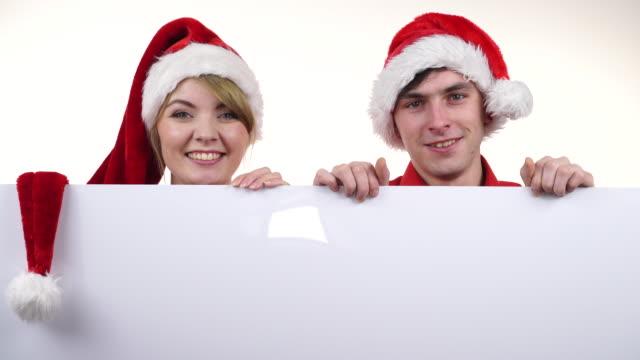 空白の空バナー ボードとカップルします。クリスマス 4 k - サンタの帽子点の映像素材/bロール