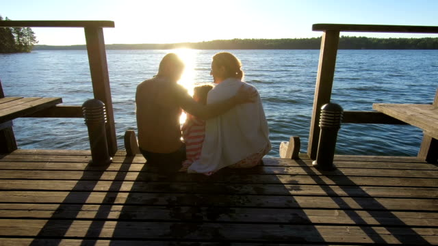 Couple with child sitting on a wooden jetty at sunset near the lake