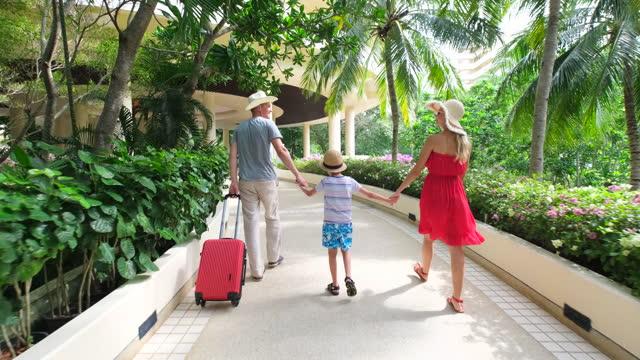 vídeos de stock, filmes e b-roll de casal com criança viajante homem mulher com mala em resort de luxo - estação turística