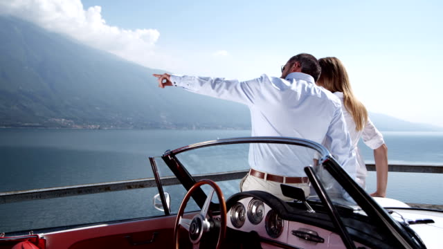 couple with convertible watching over a lake - affluent lifestyles stock videos & royalty-free footage