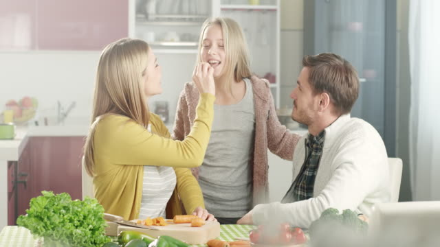 Couple with daughter enjoying in the kitchen video