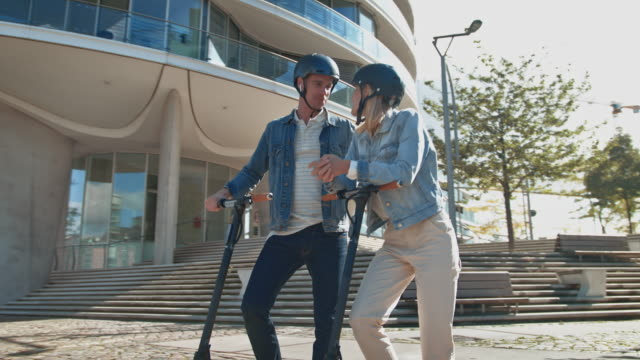 couple with electric kick scooters talking in city - monopattino elettrico video stock e b–roll