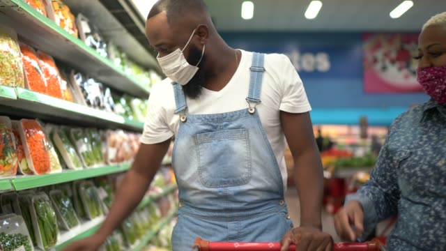 vídeos de stock e filmes b-roll de couple with face mask walking and shopping in supermarket - afro latino mask