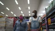 istock Couple with face mask walking and shopping in supermarket 1218025879