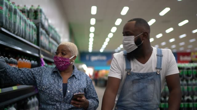vídeos de stock e filmes b-roll de couple with face mask walking and using mobile at supermarket - afro latino mask