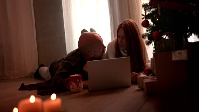 Couple with laptop and credit card doing Christmas online shopping video