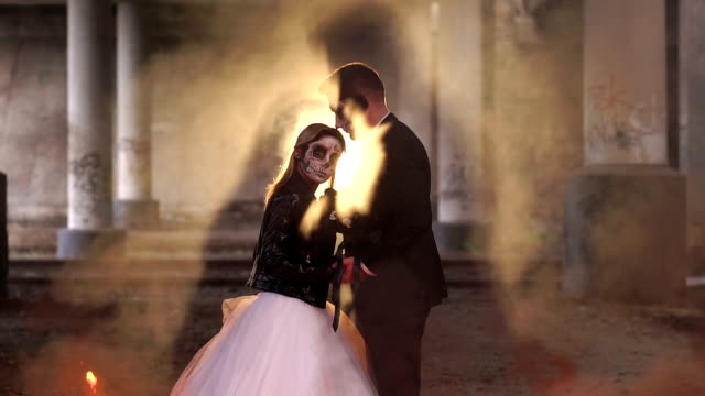 Couple with makeup for Halloween on the background of burning fire. Silhouette.