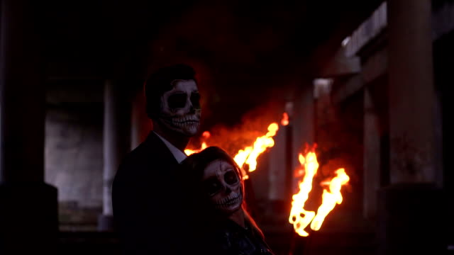 Couple with skull make-up on the background of burning fire and smoke. Halloween Couple with dark skull makeup on the background of burning fire and smoke. Halloween face art. Halloween concept. Zombie. Silhouette. Slow motion. skull stock videos & royalty-free footage