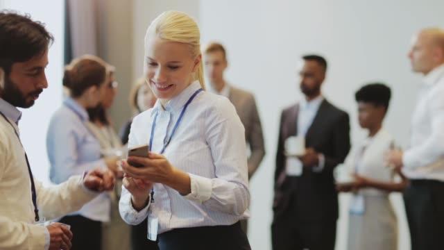 par med smartphone på business konferensen - affärskonferens bildbanksvideor och videomaterial från bakom kulisserna