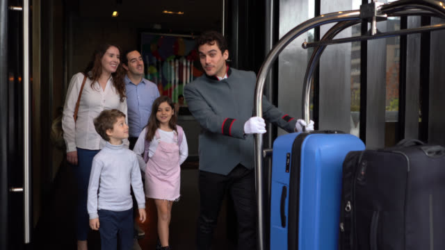 couple with their two children walking out of luxury hotel following bellhop pushing a luggage cart ready to leave - hotel checkin video stock e b–roll