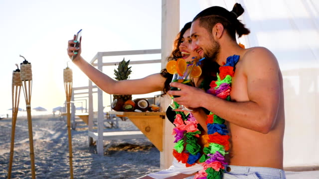 couple with wreath flowers on neck photographed on gadget, selfi guy and girl from an exotic resort video