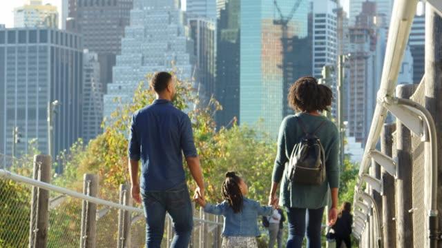 Casal com filha andando na passarela, vista traseira - vídeo