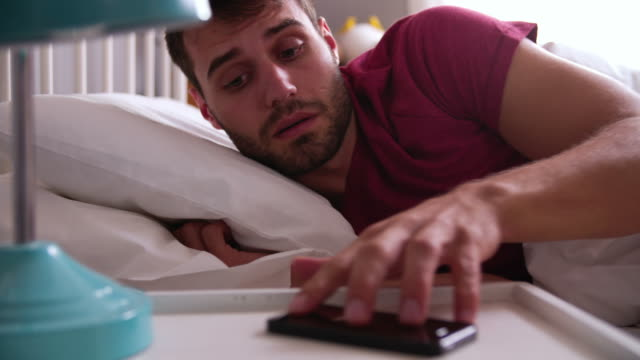 Couple Woken By Alarm On Mobile Phone Late For Work Man woken up by alarm on mobile phone - he realises he has overslept and wakes female partner before getting out of bed.Shot on Sony FS700 at frame rate of 25fps 20th century stock videos & royalty-free footage