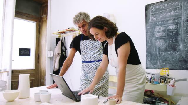 vídeos de stock, filmes e b-roll de casal trabalhando juntos em laptop em uma oficina de cerâmica - cerâmica artesanato