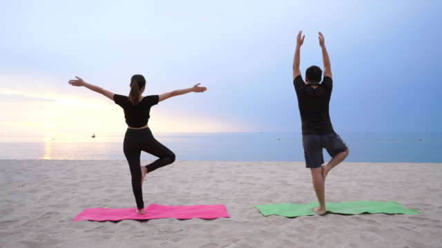 Couples are playing yoga On the beach