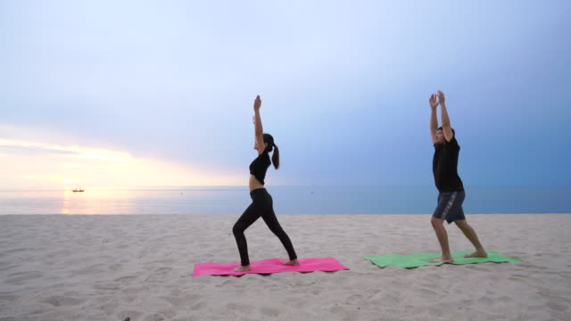 Video Couples are playing yoga On the beach