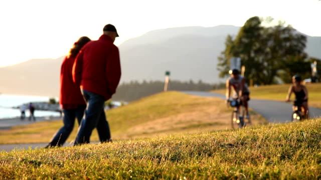 vídeos de stock e filmes b-roll de casais caminhar & bicycling - vancouver