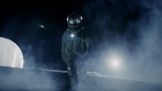 mutige astronauten im raumanzug hält taschenlampe und erforscht mysteriöse alien planet im nebel bedeckt. abenteuer. raumfahrt, bewohnbaren welt und kolonisierung konzept. - raumanzug stock-videos und b-roll-filmmaterial