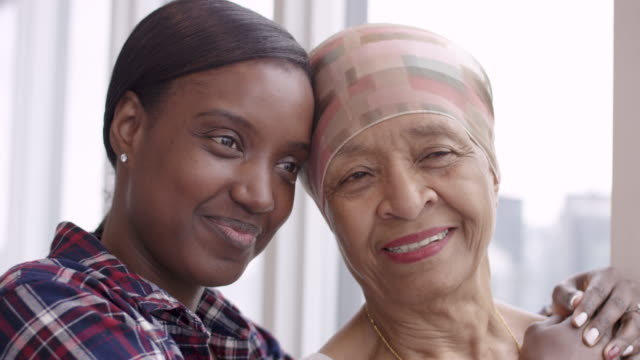 Courageous woman with cancer spends precious time with adult daughter A black senior woman with cancer is wearing a scarf on her head. Her adult daughter is giving her a hug. Both women are smiling with gratitude and hope for recovery. cancer patient stock videos & royalty-free footage