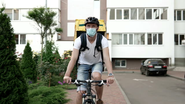 Courier delivery of food by bicycle during an outbreak of the virus. Coronavirus, COVID-19, safe delivery. video