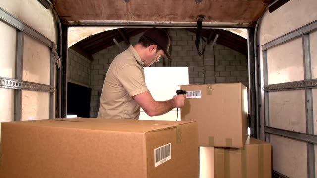 Courier / Delivery person scanning barcode on parcel in Delivery Truck video