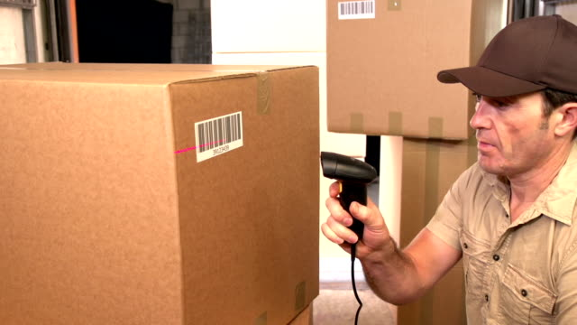 Courier / Delivery person scanning barcode on parcel in Delivery Van video