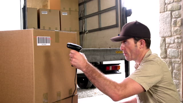 Courier / Delivery scanning barcode on parcel in Warehouse - Close up video