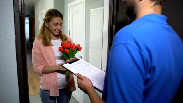 Courier giving bouquet of flowers to pretty girl, client signing delivery order