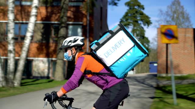 vidéos et rushes de un coursier dans un masque médical conduisant un vélo autour de la ville. - livre