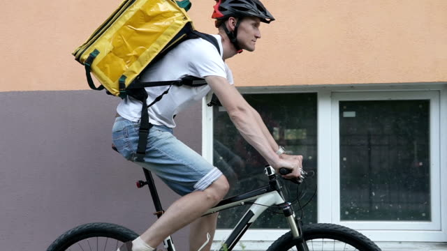 A courier in a protective helmet makes delivery of the order to customers by bicycle in the city center. video
