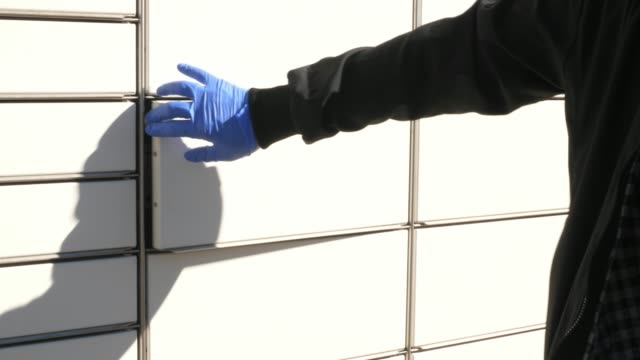 courier in protective gloves inserting placing package in box in parcel locker courier in protective gloves inserting placing package in box in parcel locker locker stock videos & royalty-free footage