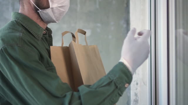vídeos de stock e filmes b-roll de courier is delivering the ordered products home to the customer during pandemic - entregar