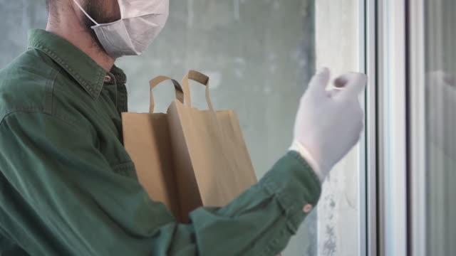 kurye pandemik sırasında müşteriye sipariş ürünleri eve teslim ediyor - sipariş vermek stok videoları ve detay görüntü çekimi