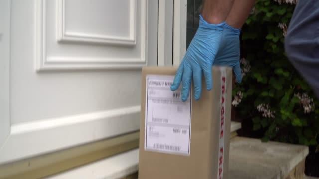 kurye parsel teslim etmek için kapıyı çalıyor - sahanlık stok videoları ve detay görüntü çekimi