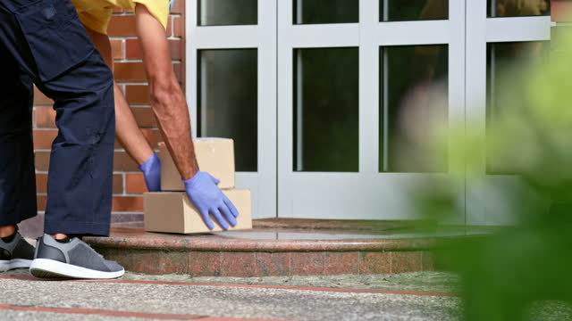 bir aile evinin kapısına paketleri bırakan kurye - sahanlık stok videoları ve detay görüntü çekimi