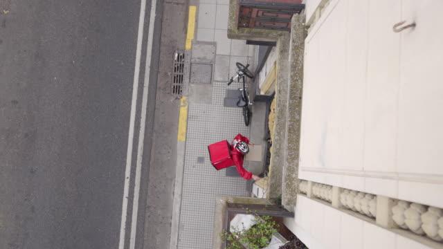 住宅樓前騎自行車的快遞員 - food delivery 個影片檔及 b 捲影像